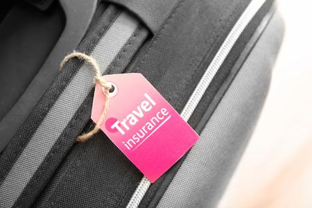 Black suitcase with label, closeup. TRAVEL INSURANCE concept