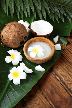 Composition with coconuts and palm leaf on wooden background
