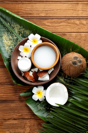 Composition with coconut milk and exotic flowers on wooden background