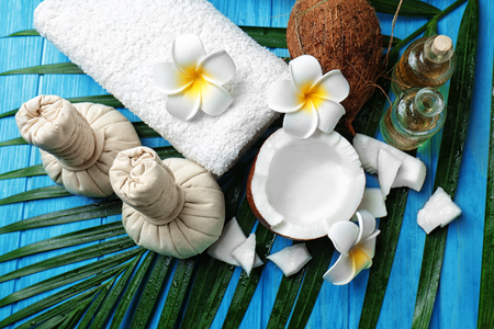 Spa composition with coconuts and palm leaf on wooden background Stock Photo