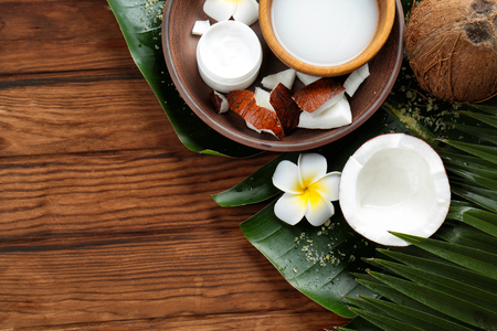 Composition with coconut milk and exotic flower on wooden background Stock Photo