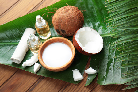 Spa composition with coconut and palm leaf on wooden background Stock Photo
