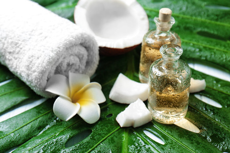 Bottles of oil, coconut, towel, tropical flower and leaf, closeup