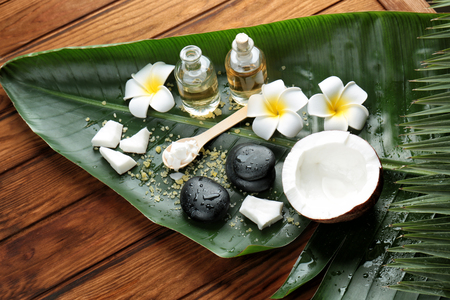 Coconut spa setting with palm leaf on wooden background
