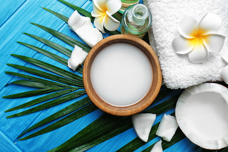 Spa composition with coconut milk and palm leaf on wooden background