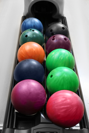 Colorful balls on rack in bowling club Stock Photo