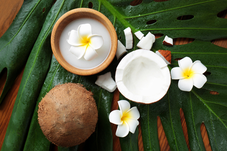 Composition with coconut milk and exotic flowers on palm leaf