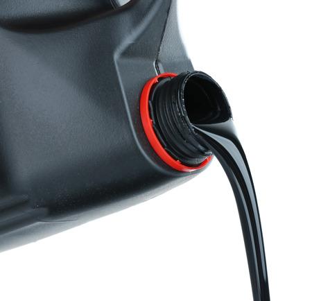 Öl, das aus schwarzem Plastikbehälter auf weißem Hintergrund herausgießt Standard-Bild
