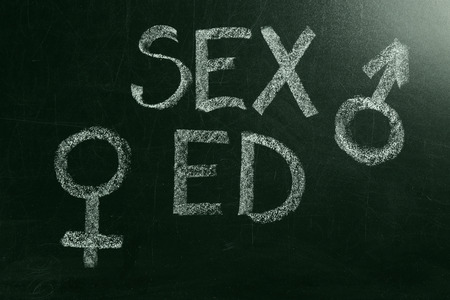 School blackboard with text SEX ED and drawn gender symbols, closeup