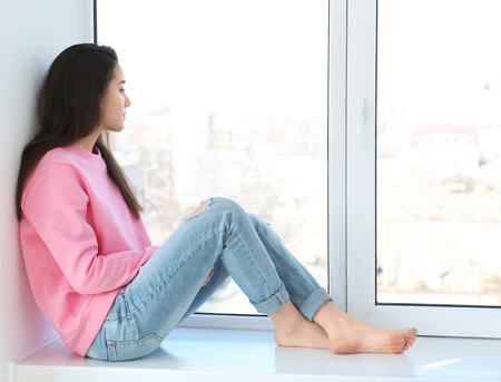 Beautiful young woman resting on windowsill