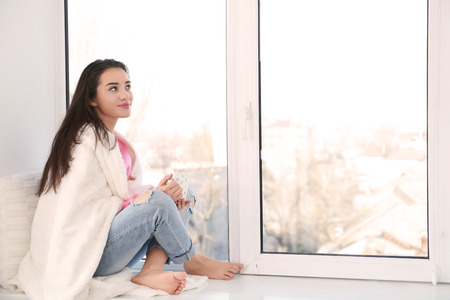Beautiful young woman with cup of coffee sitting on windowsill Stok Fotoğraf