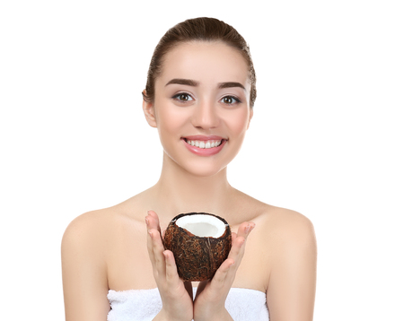 Beautiful young woman holding coconut on white background Stock Photo