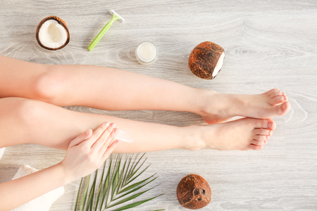 Woman applying coconut oil onto skin on wooden background Imagens