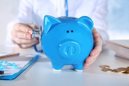 Doctors hands with piggy bank, closeup