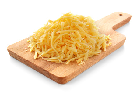 Planche de bois avec du fromage râpé sur fond blanc
