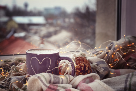 Cup of hot tasty coffee with garland and warm plaid on windowsill 免版税图像