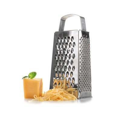 Metal grater and piece of cheese on white background Standard-Bild