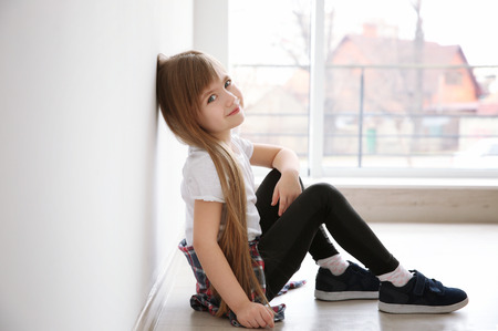 Cute little girl sitting on floor near window. Fashion concept