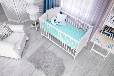 Innenraum des hellen gemütlichen Babyzimmers mit Kinderbett und Bettwäsche