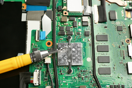 Motherboard in dismantled laptop and screwdriver, closeup. Concept of computer repair