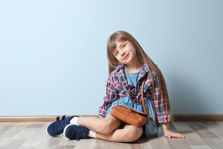 Cute little girl sitting on floor. Fashion concept