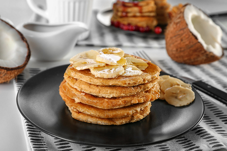 Stack of delicious coconut pancakes with sweet sauce and sliced banana on table Stock fotó