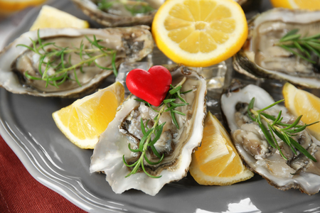 Tasty fresh oysters with sliced lemon and rosemary on plate. Aphrodisiac food for increasing sexual desire