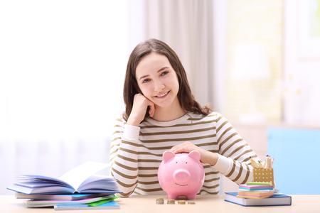 Uśmiechnięta dziewczyna siedzi przy stole z piggy bank i papeterii. Oszczędzanie na koncepcję edukacji