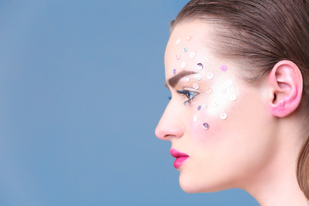 Beautiful young woman with creative make up on color background