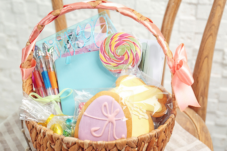 Easter basket with cookies, candy and stationery on wooden chair