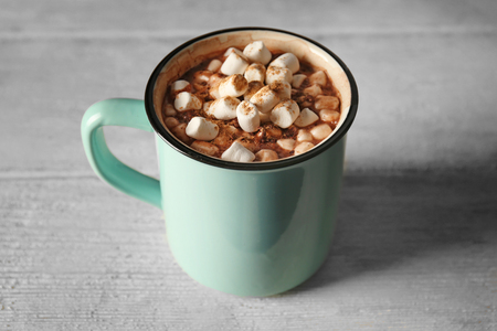 Cup of cocoa with marshmallows on wooden table