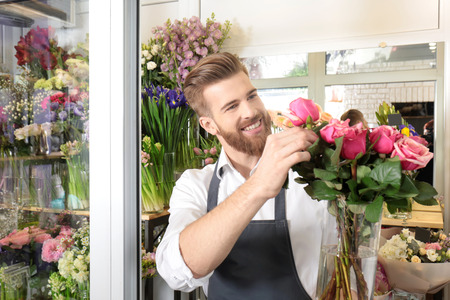 Young handsome florist with beautiful bouquet at flower shop Standard-Bild