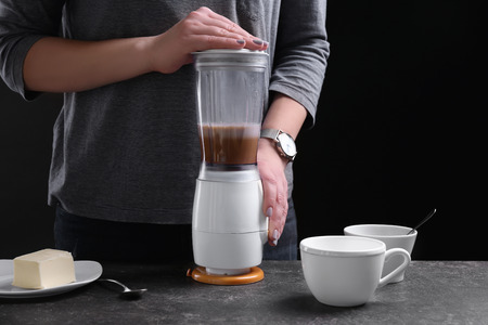 Woman using blender to make coffee with butter, closeup Stock Photo