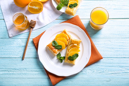 Tasty puff pastry dessert with orange and mint on served table