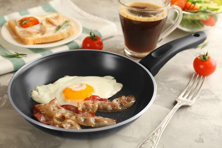 Bratpfanne mit leckerem Ei und Speck zum Frühstück auf dem Tisch