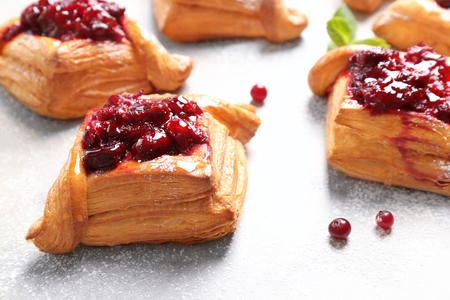 Delicious pastries with cherry jam on light background Фото со стока