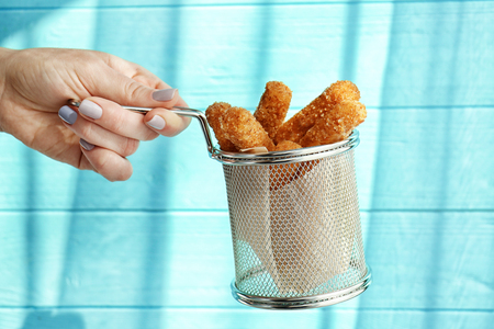 Female hand holding metal basket with cheese sticks on color background