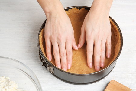 Woman making tasty cheesecake on kitchen