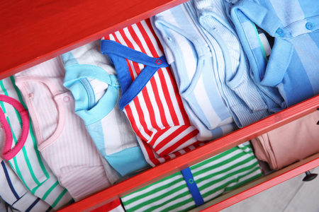Folded baby clothes in chest of drawers 免版税图像