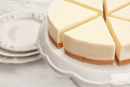 Dessert stand with delicious sliced cheesecake on table