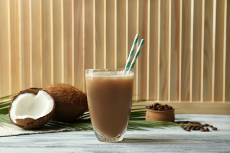 Glass with coconut coffee and straws on wooden background