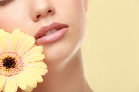Closeup view of beautiful young woman with natural lips makeup and flower on color background Фото со стока