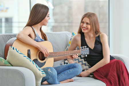Encantadora pareja con guitarra en sala de luz