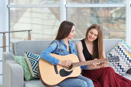 Lovely lesbian couple with guitar in light room