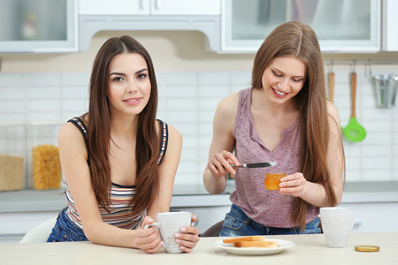 Lovely lesbian couple having breakfast together in light kitchen Stock fotó
