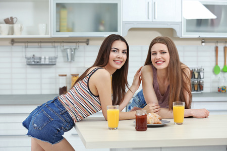 Lovely lesbian couple having breakfast together in light kitchen Stockfoto