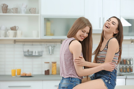 Lovely lesbian couple together in light kitchen Banque d'images