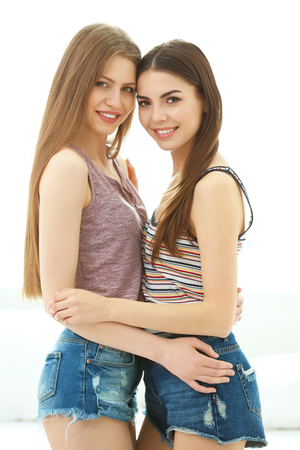 Lovely lesbian couple hugging in light room