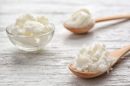 Shea butter in spoons and bowl on wooden background, close up Stock fotó