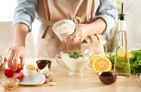 Woman preparing mayonnaise in kitchen Imagens